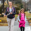 Jade, 9, and her mother stroll down a sidewalk in Clarksville, heading toward future Girl Scout Cookie customers. Staff Photo By Josh Hicks
