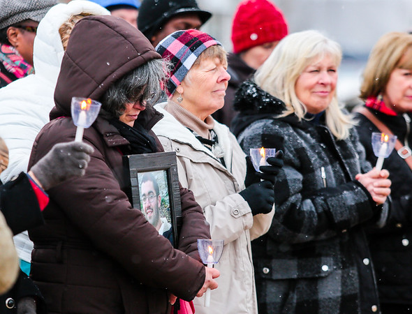 Celina Acosta, left, holds a portrait of her late son as she stands with Pam Weber, middle, and Terri Poff during the Clark County Cares candlelight vigil honoring those who lost their lives to drug addiction at the base of the Big Four Bridge on Sunday. Staff Photo By Josh Hicks