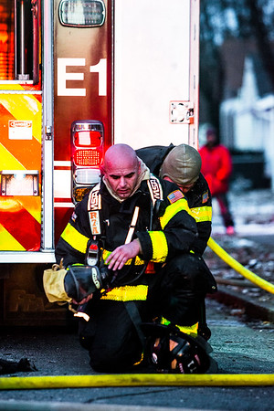 A New Albany firefighter gets an oxygen tank mounted to his back before tackling a house fire that occurred on the 1700 block of East Elm Street in New Albany Saturday evening. Staff Photo By Josh Hicks