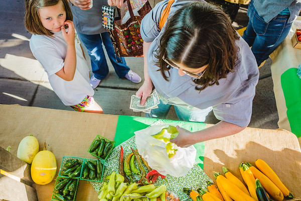 Chef Gina Brown picks up 15 banana peppers for pickling at the New Albany Farmers Market on Saturday. Staff Photo By Josh Hicks