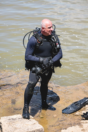 Louisville Metro Police Officer Del Gallagher clutches his diving mask during a break on shore.