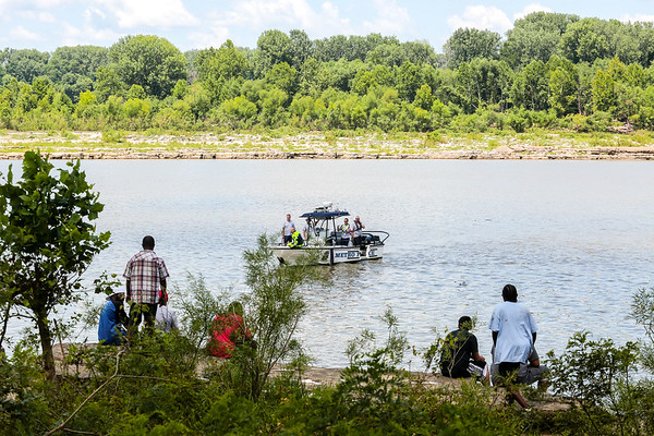 "Family and friends of Marcus ""Shawn"" Williams, 41, of Jeffersonville, wait for good news on the edge of the Ohio River as a Louisville Metro Police boat coasts in the water during Saturday's rescue operation. Staff Photos By Josh Hicks"