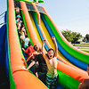 Cameron Clark, 11, pumps his fists in the air at the foot of a tall, inflatable water slide during Summer Explorers on at Gateway Park Wednesday.
