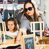 Gwen Earl, 8, left and her mother Chef May Earl pick through baskets at the New Albany Farmers Market on Saturday. Staff Photo By Josh Hicks