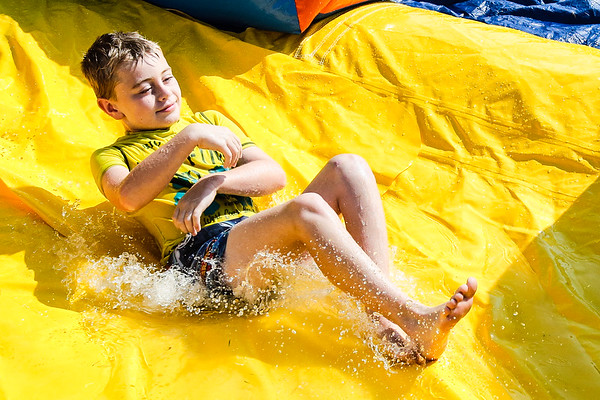 Joey Winebrenner, 8, splashes down an inflatable water slide during Summer Explorers, a free program for children ages 7 to 12, at Gateway Park on Wednesday. Staff Photos By Josh Hicks