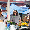 Chefs Gina Brown, right, and May Earl stop at Lost Creek Acres' booth for some garlic and baby squash at the New Albany Famers Market on Saturday. Staff Photo By Josh Hicks