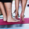 Finger tips reach for toes during the yoga class on the RiverStage on Saturday.