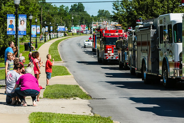 Attendees wave to passing fire trucks during the Charlestown Founder's Day parade on Saturday. Staff Photos By Josh Hicks