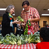 Jim and Shay Grahn add broccoli to a bag for their daughter and themselves while at the Fresh Stop Market at Wesley United Methodist Church in Jeffersonville on Thursday. Shareholders purchase into the program and come by the church twice on month on Thursdays to pick up vegetables from local farms, depending on what's in season. Staff photo by Tyler Stewart