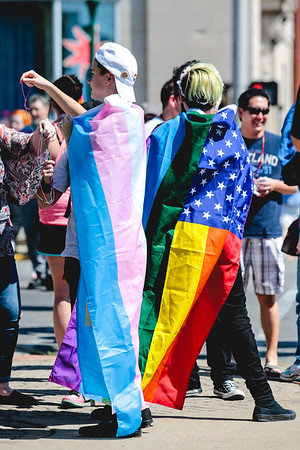 The Transsexual, left, and Homosexual flags, right, adorn the backs of attendees of the Jeffersonville Pride Festival in Warder Park on Saturday. Staff Photo By Josh Hicks