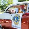 A Charlestown Lions Club member tosses a piece of candy from a vintage car during the Charlestown Founder's Day parade.