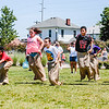 Kids leap forward during a potato sack race during Jeff Fest at Big 4 Station on Saturday. Staff Photo By Josh Hicks