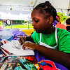 Niyah Cooper, 7, draws during Art on the Parish Green at St. Paul's Episcopal Church on Saturday. Staff Photo By Josh Hicks