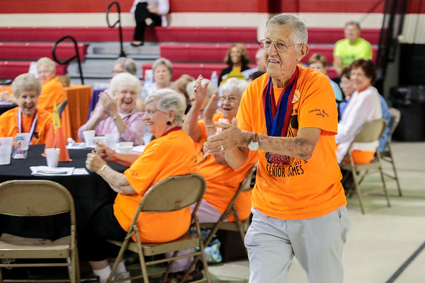 Clarence Schaftlein goes up to the podium to receive his medal for winning the most medals in his age group at the closing ceremony of the Senior Games at Sacred Heart in Jeffersonville on Friday. He also won a trophy for being the oldest male competitor at the age of 93. Staff Photo By Josh Hicks