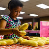 Volunteer Dara Brandt, 6, organizes summer squash for shareholders to pick up with their orders at the Fresh Stop Market at Wesley United Methodist Church in Jeffersonville on Thursday. Staff photo by Tyler Stewart