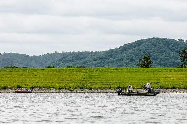 Two pairs of people fish on Deam Lake against a scenic background on Thursday.