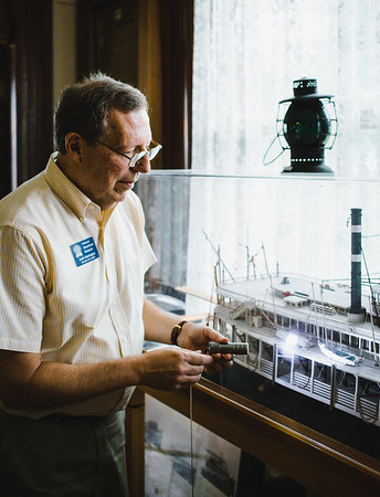 Keith Norrington inspects a model of a steamboat with a flashlight at the Howard Steamboat Museum.