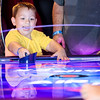 Hunter Adams, 4, rejoices after scoring a point during a game of air hockey at Strike and Spare Family Fun Center in Clarksville on Friday. Staff Photo By Josh Hicks