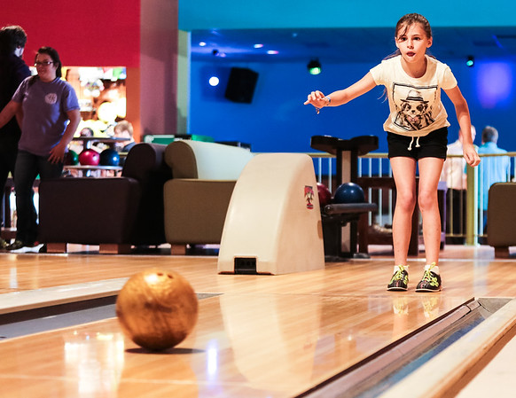 Nicole Weathers, 10, waits for her ball to make its way down the lane at Strike and Spare Family Fun Center in Clarksville on Friday. Staff Photo By Josh Hicks