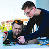 Drone racers Gary Roberts, left, and Cameron Fiorini work on repairing a drone during the drone flying competition at the New Albany amphitheater on Saturday. Staff Photo By Josh Hicks