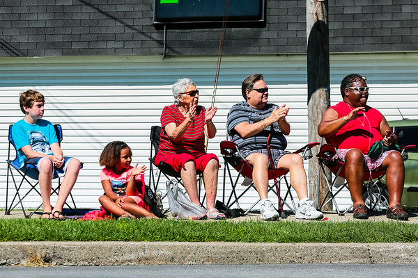 People plant themselves along Market Street in Charlestown to clap and wave for the Founder's Day parade.