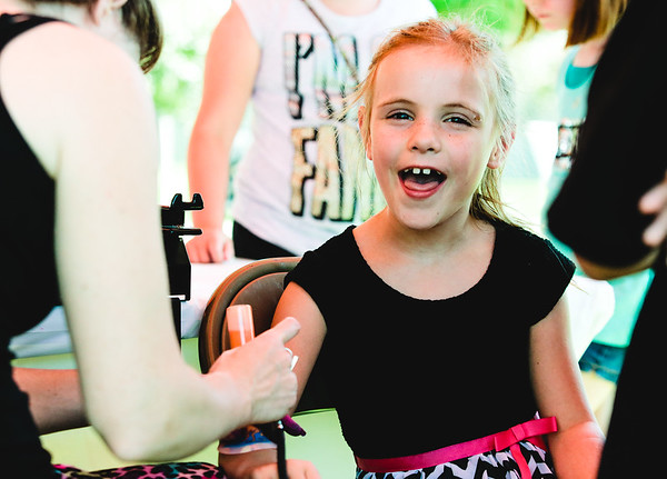 Zoe Johnson, 7, gets an airbrush tattoo from Kid Canvas Face Painting during Jeff Fest at Big 4 Station on Saturday. Staff Photo By Josh Hicks