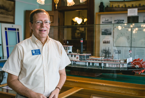 Keith Norrington, Director & Curator of the Howard Steamboat Museum, poses in front of a model of the Chicot, a tow boat that was built in 1925. Staff Photos By Josh Hicks