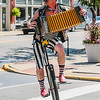 Jacek the Strange rides his unicycle and plays acordian during the Jeffersonville Pride Parade on Saturday. Staff Photo By Josh Hicks