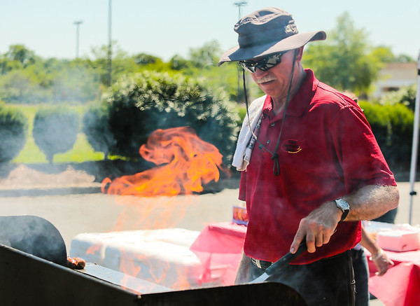 Horizon Bank Vice President and grillmaster Kevin Burkes tends to some hamburgers during the Jeffersonville Fire Department and First Harrison Bank WHAS Crusade for Children cookout on Friday. Staff Photo By Josh Hicks
