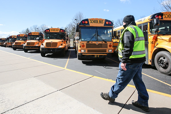 Jeffersonville High School safety specialist Gary Green walks along a row of busses full of students waiting to be taken home on Friday. Staff Photo By Josh Hicks