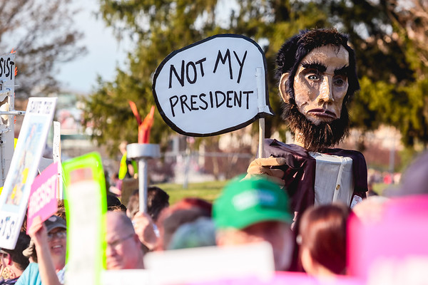 An Abraham Lincoln puppet gauntly expresses its opinion on a speech bubble sign in opposition to President Donald Trump's rally in Louisville on Monday. Staf Photo By Josh Hicks