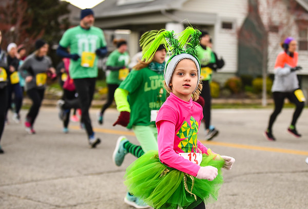 Rebecca Johnson, 5, Jeffersonville, runs along Chestnut Street with the rest of the Leprechaun Run participants Tuesday. Staff photo by Tyler Stewart