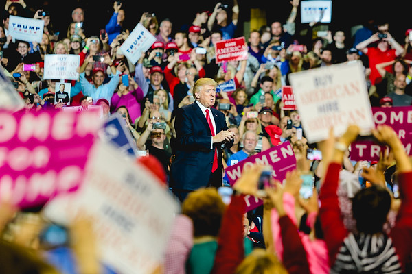 President Donald Trump takes the stage, surrounded by cheering supporters waving signs at his rally in Louisville on Monday. Staff Photo By Josh Hicks
