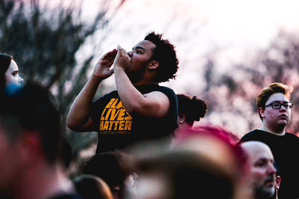 """A protester wearing a """"Black Lives Matter"""" t-shirt leads in a chant outside the entrance of the Kentucky Exposition Center during Donald Trump's rally in Louisville on Monday. Staff Photo By Josh Hicks"""