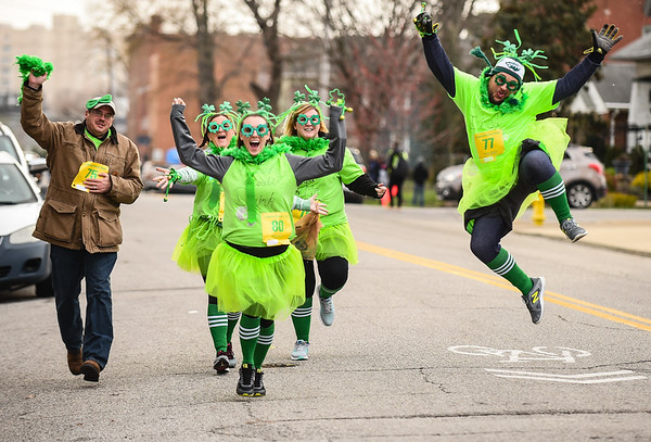 A leaping Greg Tureson, right, and fellow Chase Bank employees travel along Chestnut Street while participating in the annual Leprechaun Run in Jeffersonville on Tuesday. Staff photo by Tyler Stewart