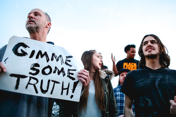 "A man holding a sign reading, ""Gimme Some Truth!"" stands among fellow Trump protesters outside of the Kentucky Expostion during the President's rally in Louisville on Monday. Staff Photo By Josh Hicks"