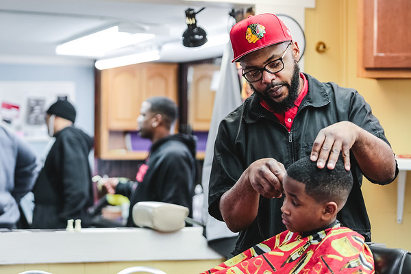 Eron focuses on giving 7-year-old Keshuan Muckle a trim at Mark's Barber and Style in Jeffersonville. Staff Photo By Josh Hicks