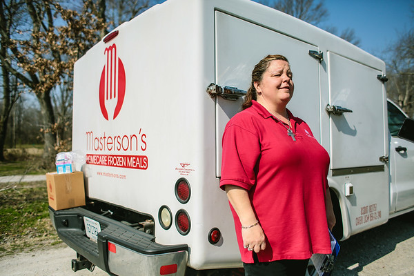 Gina Lockwood stands near her Masterson's homecare frozen meal delivery truck with a weeks worth of food waiting to be delivered on the bumper. Staff Photo By Josh Hicks