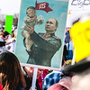 A protester hoists a sign featuring Vladimir Putin holding up President Donald Trump. Staff Photo By Josh Hicks