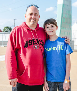 Jeffersonville's Ronnie Conway, left, and his son Brett, 11, spend their day off from parking cars to enjoy some Beatles music during the opening day of Abbey on the River at Big Four Station. Brett has volunteered to park cars with his Clark County Boy Scout Troop. Staff Photo By Josh Hicks