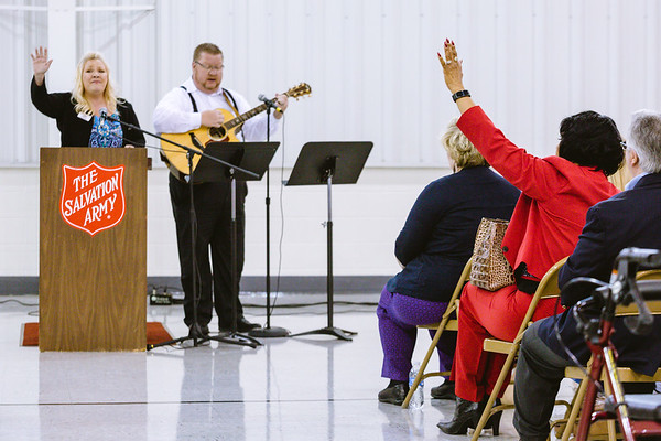 An attendee of the National Day of Prayer raises her hand in celebration as Angie Graf, left, and Dan Graf lead a group in song at the Salvation Army in New Albany on Wednesday. Staff Photo By Josh Hicks