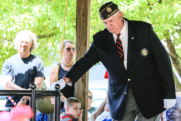 Vietnam veteran Jack Wayne places a flower into a helmet in honor of a fallen soldier during the Sellersburg Memorial Day service at Wilkerson Park on Monday. Staff Photo By Josh Hicks