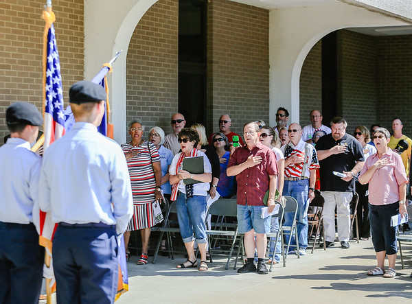 "Attendees of the Clark County Memorial Day service put their hands over their hearts and sing ""The Star-Spangled Banner"""