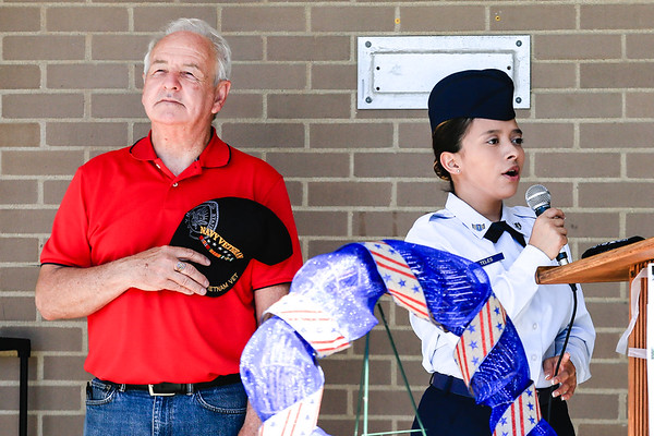 """County Commissioner Jack Coffman places his hat over his heart as Jeffersonville Air Force JROTC Cadet Airman First Class Maria Teles sings """"The Star-Spangled Banner"""" during the Memorial Day service at the Clark County Government building on Monday. Staff Photo By Josh Hicks"""