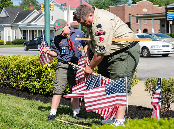 Drake Rupprecht, 9, left, and his father Craig Rupprecht, Clubmaster of Clarksville's Troop 4010, accurately space out flags using a yard stick in the front lawn of the Clark County Courthouse building on Friday. Staff Photo By Josh Hicks