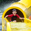 Jadon Russell, 7, emerges from a slide at Clarksville Cove in the rain after the water park's ribbon cutting on Thursday. Staff Photo By Josh Hicks