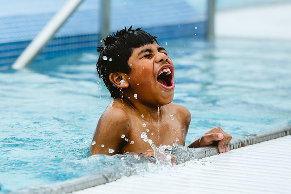 Roberto Teliz, 8, pops up out of the water in the lap pool at Clarksville Cove in the rain after the water park's ribbon cutting on Thursday. Staff Photo By Josh Hicks