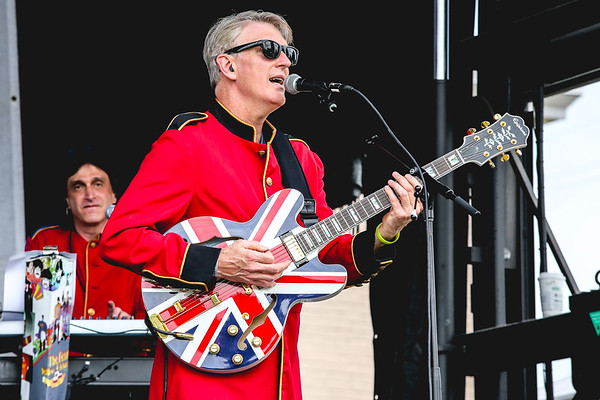 Troy Clampitt of the Rigbys plays his Union Jack style guitar during Abbey Road on the River on Saturday. Staff Photo By Josh Hicks