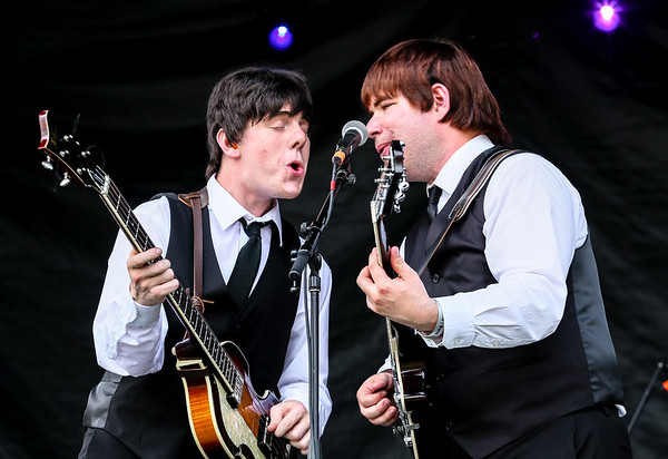 "Al Francis as Paul McCartney, left, and Robert Murray as George Harrison share a microphone during Studio 2's performance of ""Twist and Shout"" during Abbey Road on the River on Saturday. Staff Photo By Josh Hicks"