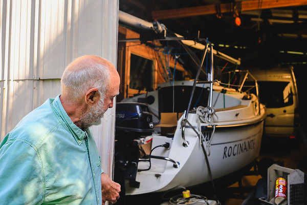 Carl DeGraff pulls back a barn door, revealing his sailboat. Staff Photo By Josh Hicks